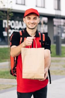 Eten bezorger bestellen bij een restaurant knappe jongeman in een t-shirt en een pet blije bezorging