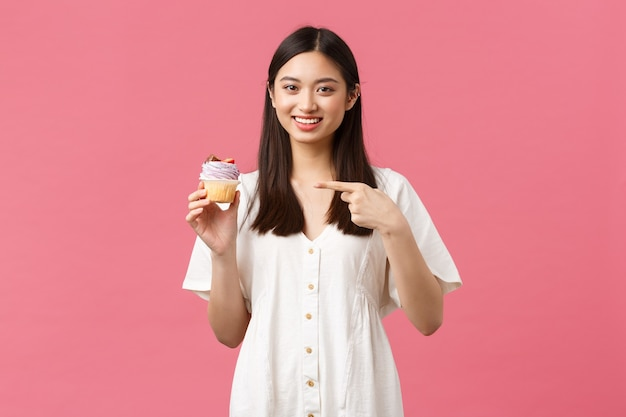 Eten, café en restaurants, zomer lifestyle concept. gelukkige aziatische vrouw tevreden met geweldige smaak van dessert, wijzend op cupcake beveelt bakkerijwinkel aan, staande roze achtergrond.