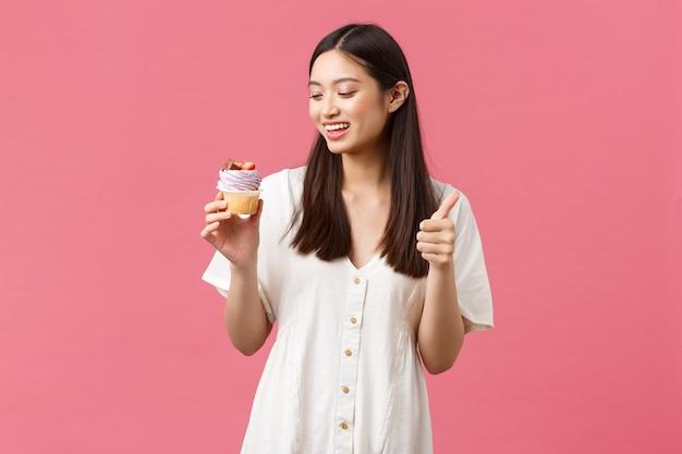 Eten, café en restaurants, zomer lifestyle concept. glimlachende gelukkige vrouwelijke klant beveelt heerlijke cupcake aan in de bakkerijshow, duimen omhoog en kijkend naar het dessert met verlangen om te bijten