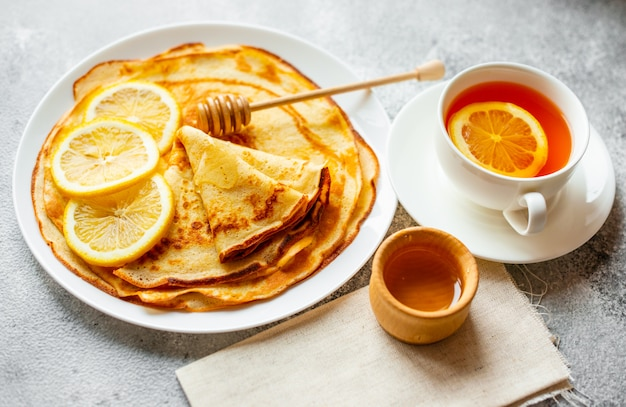 Eten, dessert, gebak, pannenkoek, taart. smakelijke mooie pannekoeken met banaan en honing op een concrete achtergrond