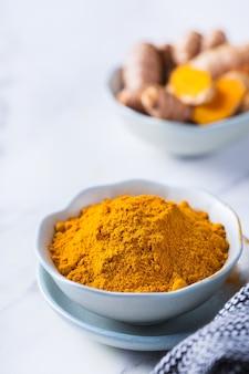 Eten en drinken, dieetvoeding, gezondheidszorgconcept. rauwe biologische oranje kurkuma wortel en poeder, curcuma longa op een kooktafel. indiase oosterse kruiden met een laag cholesterolgehalte