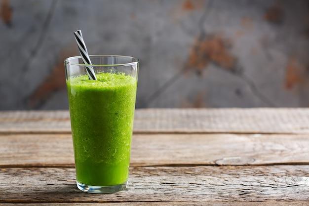 Eten en drinken, gezond dieet en voeding, levensstijl, veganistisch, alkalisch, vegetarisch concept. groene smoothie met biologische ingrediënten, groenten op een houten keukentafel. ruimte achtergrond kopiëren