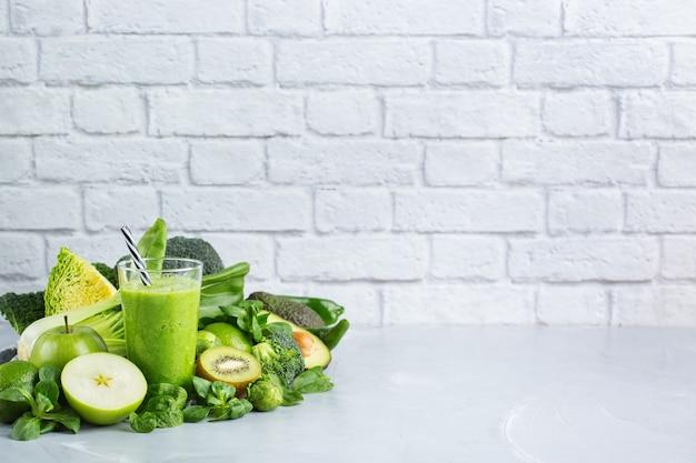 Eten en drinken, gezond dieet en voeding, levensstijl, veganistisch, alkalisch, vegetarisch concept. groene smoothie met biologische ingrediënten, groenten op een moderne keukentafel. ruimte achtergrond kopiëren
