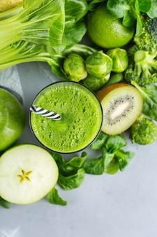 Eten en drinken, gezond dieet en voeding, levensstijl, veganistisch, alkalisch, vegetarisch concept. groene smoothie met biologische ingrediënten, groenten op een moderne keukentafel