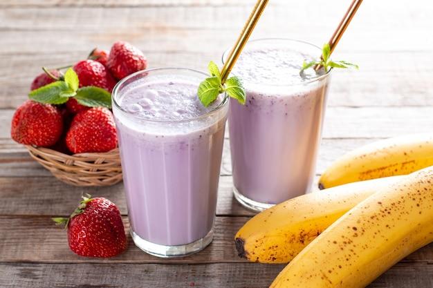 Eten en drinken, gezond dieet en voeding, levensstijl, veganistisch, alkalisch, vegetarisch concept. roze smoothie met banaan en aardbei op oude houten achtergrond.