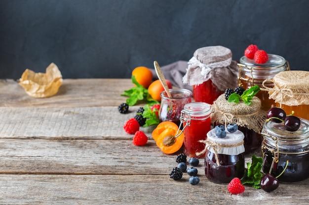 Eten en drinken, oogst zomer herfst concept. assortiment van seizoensgebonden bessen en fruit jam in potten op een houten tafel. ruimte rustieke achtergrond kopiëren