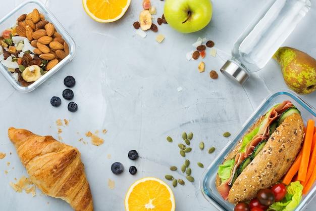 Eten en drinken, stilleven, dieet en voeding, gezond eten, afhaalconcept. lunchbox met boterham, fruit, groenten, notenmix en flesje water. bovenaanzicht plat lag, kopieer ruimte achtergrond