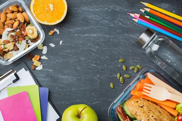 Eten en drinken, stilleven, dieet en voeding, gezond eten, afhaalconcept. school lunchdoos en briefpapier. bovenaanzicht plat lag, kopieer ruimte schoolbord achtergrond