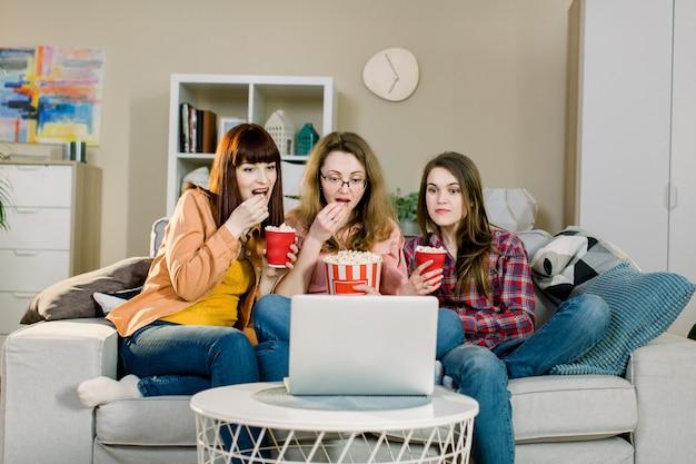 Eten en films. drie emotionele mooie zusters die popcorn eten tijdens het kijken naar een film of sportprogramma terwijl ze op de bank van een mooie kamer thuis zitten.