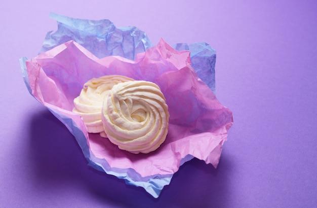 Eten foto van zelfgemaakte zephyr, marshmallow in violet inpakpapier. gezond zoet dessert op een roze achtergrond.