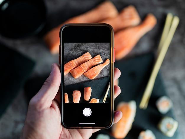 Eten fotograferen. handen nemen van foto's van heerlijk aziatisch eten