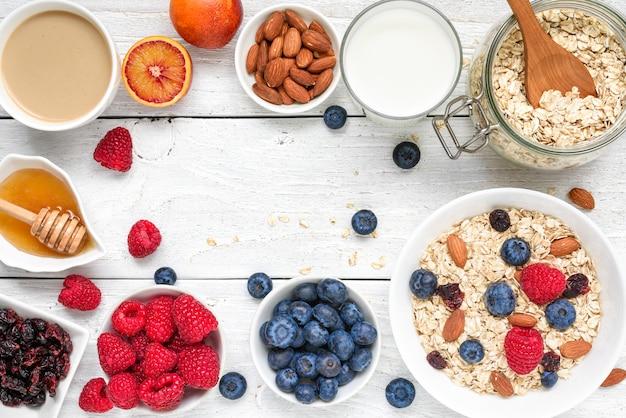 Eten frame gemaakt van ontbijt ingrediënt. muesli, fruit, bessen, cappuccino, nony, melk en noten. gezond eten