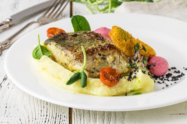 Eten - hoofdgerecht gastronomische vis - heerlijke gegrilde gouden zeebrasem of dorade met groentegarnituur geserveerd op een houten tafel