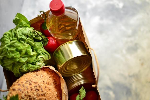 Eten in een papieren zak. voedselschenking of voedselbezorging concept. . olie, brood, kool, salade, groenten, conserven. bovenaanzicht