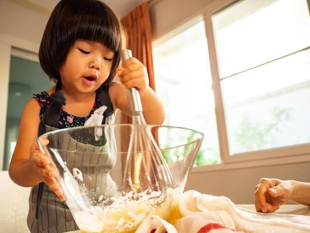Eten klasse familie in keuken kamer met haar kind. aziatische mensen doen samen activiteiten thuis.