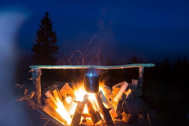 Eten koken in de pot in vuur en vlam onder de blauwe nachtelijke hemel met veel sterren