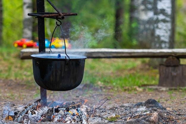 Eten koken op een kampvuur in het bos, food camping concept, plek voor een kampvuur in het landelijke huis