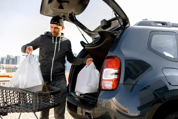 Eten kopen in een supermarkt en tassen in de auto doen.