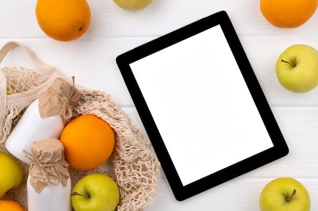 Eten kruidenier online winkelen bezorgen. eco vriendelijke natuurlijke tas met fruit en tablet op houten tafel