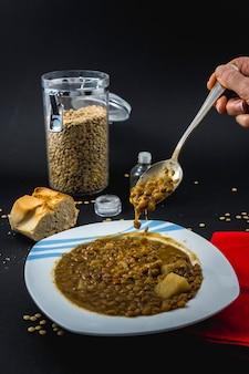 Eten met een lepel in een bord met spaanse gekookte linzen, samen met ingrediënten zout en olie