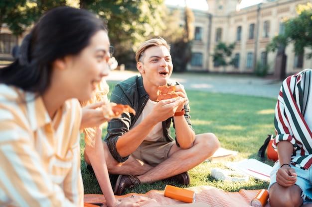 Eten met vrienden. vrolijke jongen zit met zijn vrienden op het gras op de universiteitswerf lachend en zijn pizza etend.