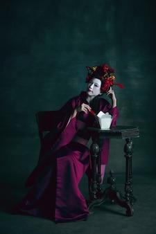 Eten smaakt goed. jonge japanse vrouw als geisha geïsoleerd op donkergroene achtergrond. retro stijl, vergelijking van tijdperken concept. mooi vrouwelijk model als een helder historisch karakter, ouderwets.