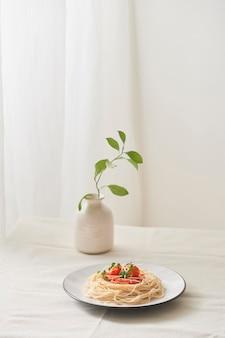Eten, spaghetti bolognesesaus in witte schaal en een vaas met planten op een witte voorbereide tafel
