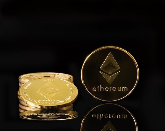 Ethereum cryptocurrency munt en gouden munten stapel ernaast op zwarte achtergrond