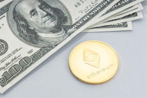 Ethereum-munt en een stapel amerikaanse dollarbankbiljetten. blockchain-geld versus fiat-geldconcept