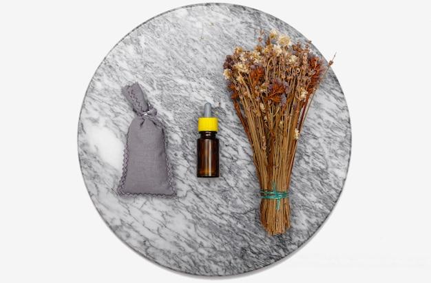 Etherische olie en lavendelbloemen. selectie van etherische olie op marmeren tafel met op de achtergrond diverse biologische kruiden en bloemen.