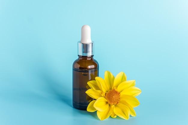 Etherische olie in bruine druppelflesje en gele bloem. concept natuurlijke organische schoonheid cosmetica product