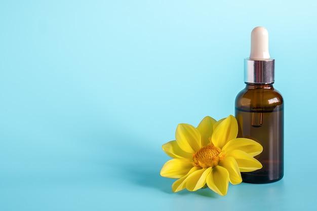 Etherische olie in bruine druppelflesje en gele bloem. concept natuurlijke organische schoonheid cosmetica product.
