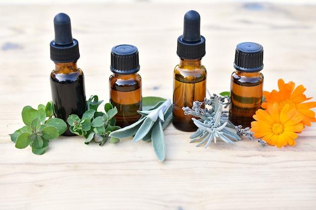 Etherische olie in bruine flessen met verse kruiden en bloemen, kruidengeneeskunde, thuisapotheker.