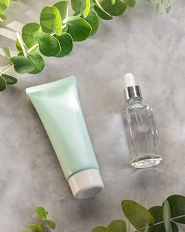 Etherische olie in druppelaar glazen fles en groene buis met gezichtslotion. hydraterend serum en crème met eucalyptusextract, huidverzorging of kruidencosmeticaconcept.