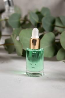 Etherische olie in druppelaar glazen fles, hydraterend hyaluron serum met eucalyptus extract, huidverzorging of lichaamsverzorging, alternatieve geneeskunde en kruidencosmetica concept, verticaal