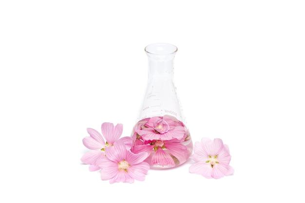 Etherische olie in een glazen fles met bloemen
