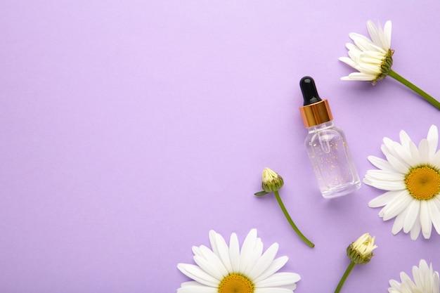 Etherische olie in glazen fles met verse kamille bloemen op paarse achtergrond. bovenaanzicht.