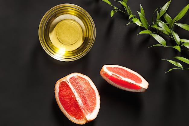 Etherische olie in glazen fles met verse, sappige grapefruit en groene bladeren-schoonheidsbehandeling.