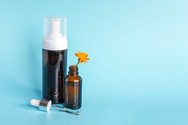Etherische olie in open bruine druppelfles met liggende glazen pipet, grote fles met witte dispenser en oranje bloem calendula