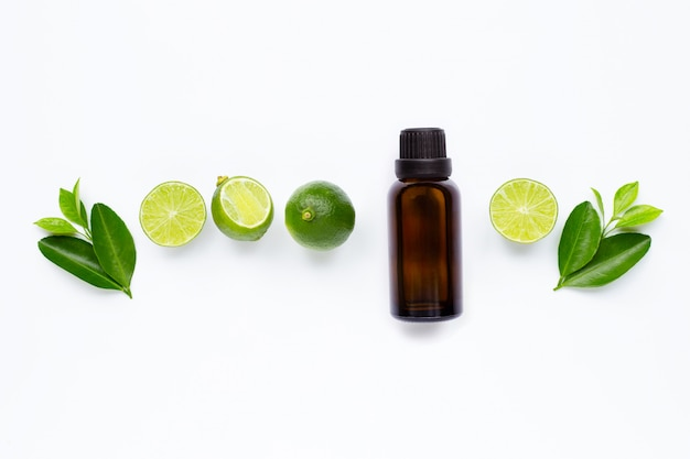 Etherische olie met limoenen en bladeren op wit wordt geïsoleerd.