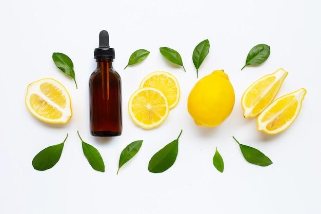 Etherische olie met verse citroen en groene bladeren op wit