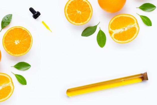 Etherische olie met verse oranje citrusvruchten en bladeren die op wit worden geïsoleerd