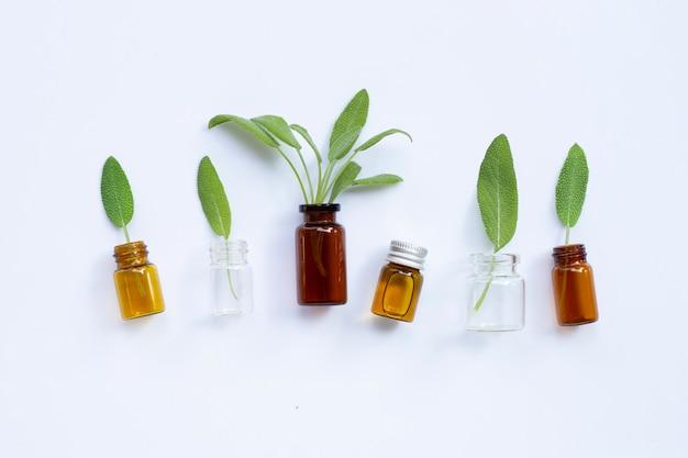 Etherische olie met verse salie bladeren op witte tafel.