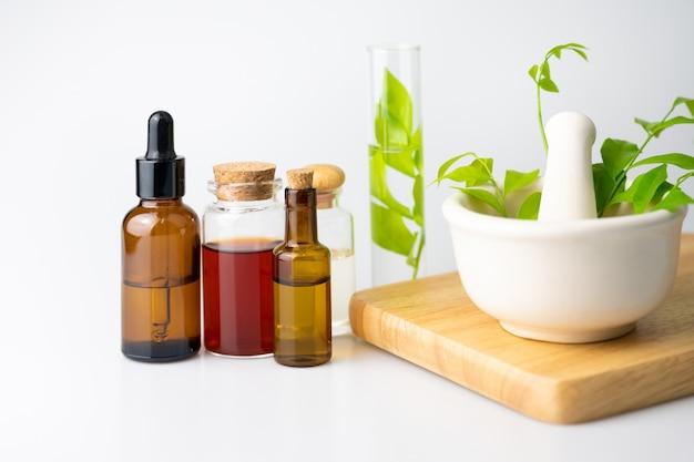 Etherische olie voor aromatherapie in glazen fles op witte tafel, kruidengeneeskunde van natuurlijke
