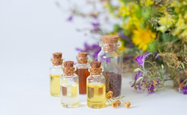 Etherische oliën in glazen flessen met organische geneeskrachtige kruiden en bloemen op de lichte achtergrond