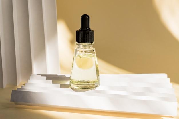 Etherische oliën met druppels pipet in de fles op beige muur