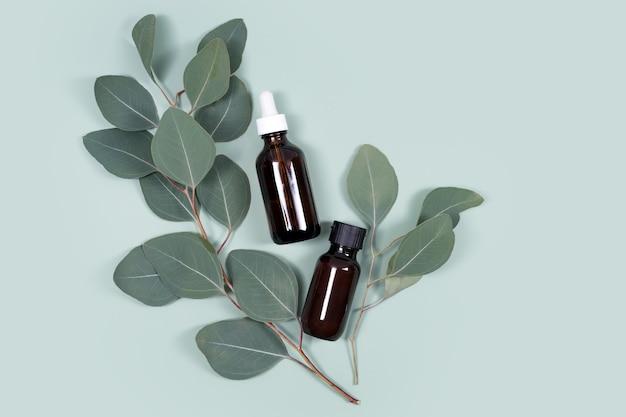 Etherische oliën met natuurlijke eucalyptusbladeren op mintgroene achtergrond, schoonheidsproducten, gezichtsverzorging, spa schoonheidsbehandeling concept