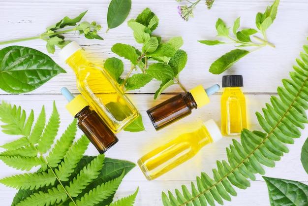 Etherische oliën natuurlijk op houten en muntblad biologisch - aromatherapie kruidenolie flessen aroma met bloembladeren varen kruidenformuleringen inclusief wilde bloemen en kruiden op hout bovenaanzicht