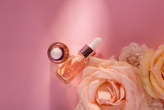 Etherische rozenolie in cosmetische fles in de buurt van verse roze bloemen tegen roze achtergrond. bovenaanzicht cosmetica plat leggen