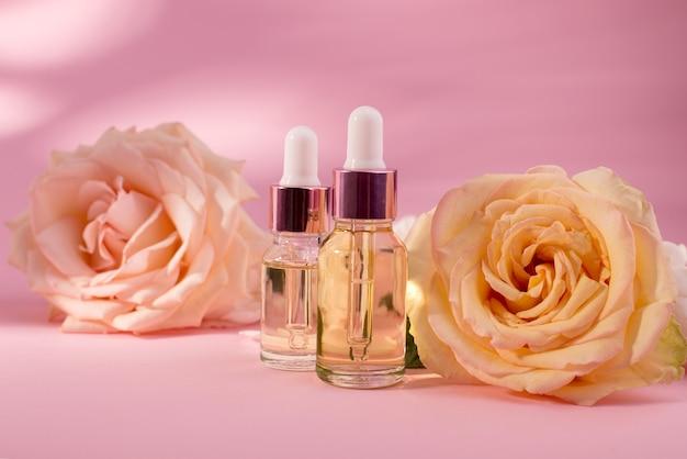 Etherische rozenolie in cosmetische fles in de buurt van verse roze bloemen tegen roze achtergrond. rozenbloem extract.